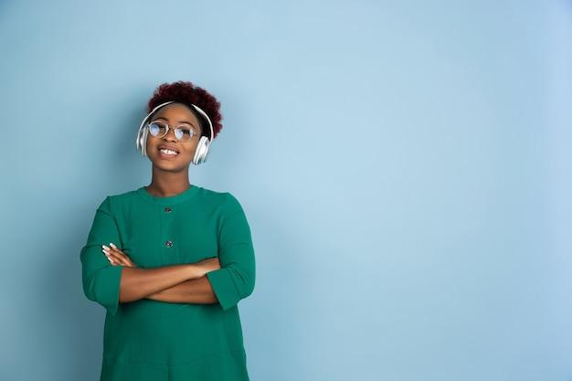 Mooie jonge vrouw die zich voordeed op blauwe muur Gratis Foto