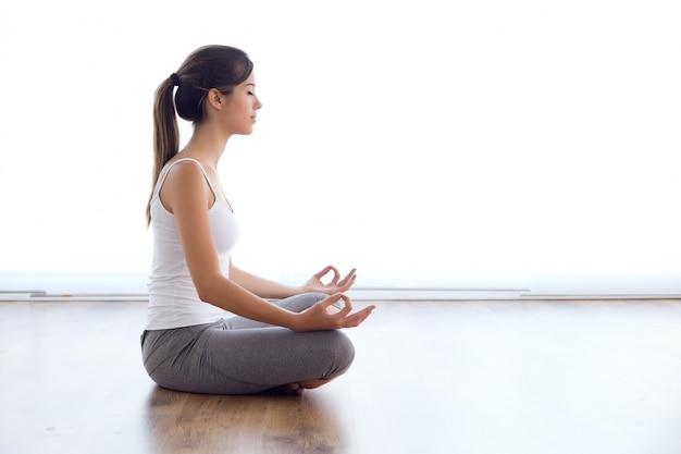 Mooie jonge vrouw doet yoga oefeningen thuis. Gratis Foto