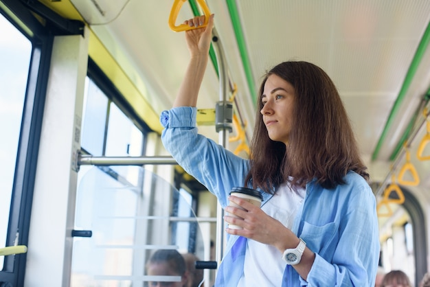 Mooie jonge vrouw drinkt heerlijke koffie in stadsbus of tram. concept van openbaar vervoer. Premium Foto