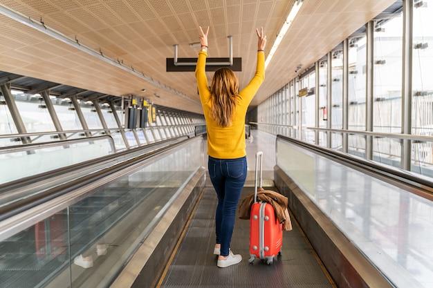 Mooie jonge vrouw erg blij met haar handen omhoog op de luchthaven met haar bagage Premium Foto