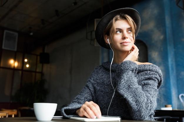 Mooie jonge vrouw gekleed in trui en hoed zit aan de café tafel binnenshuis, luisteren naar muziek met koptelefoon, koffie drinken, notities maken, wegkijken Premium Foto