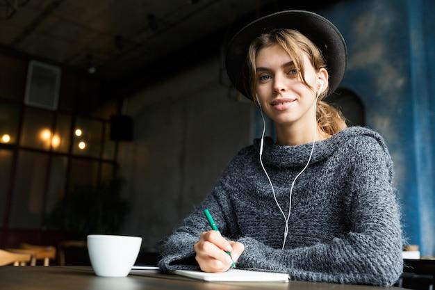 Mooie jonge vrouw gekleed in trui en hoed zit aan de café tafel binnenshuis, luisteren naar muziek met koptelefoon, koffie drinken, notities maken Premium Foto