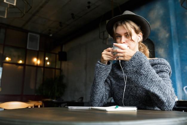 Mooie jonge vrouw gekleed in trui en hoed zit aan de café tafel binnenshuis, luisteren naar muziek met koptelefoon, koffie drinken Premium Foto