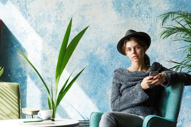 Mooie jonge vrouw gekleed in trui en hoed zittend in de stoel aan de cafétafel, met mobiele telefoon, stijlvol interieur Premium Foto