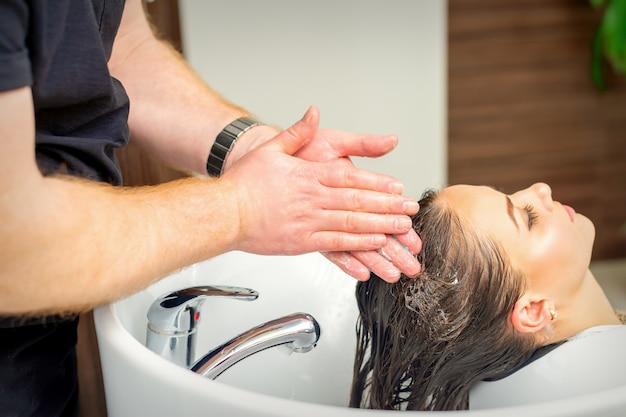 Mooie jonge vrouw haar haren wassen door handen van mannelijke kapper in kapsalon Premium Foto