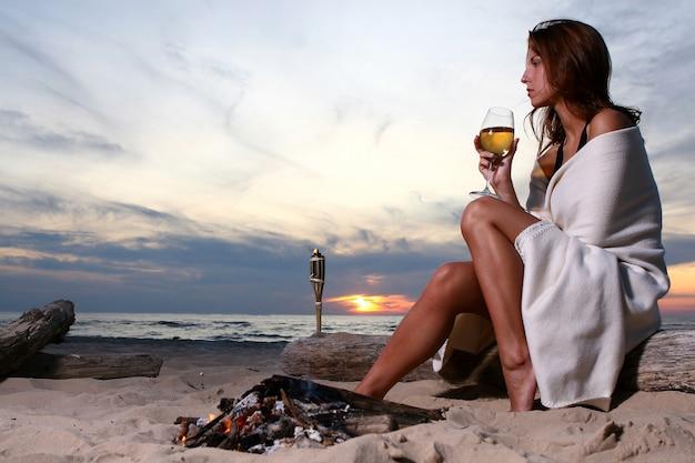 Mooie jonge vrouw het drinken wijn op strand Gratis Foto