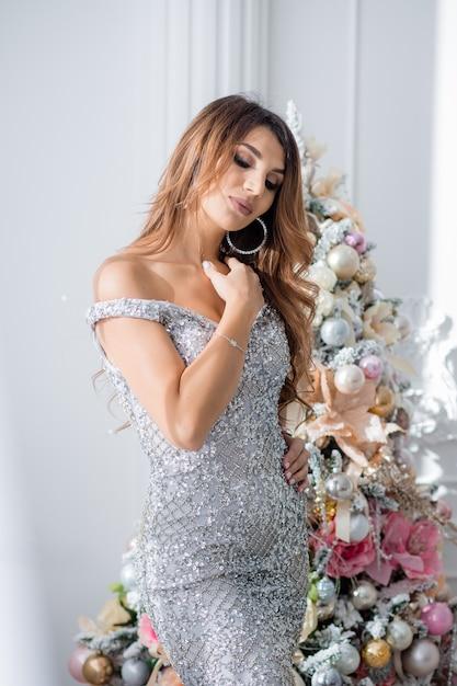 Mooie jonge vrouw in avondjurk in de buurt van de kerstboom. vrolijk kerstfeest Premium Foto