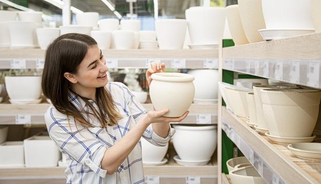 Mooie jonge vrouw in een bloemenwinkel kiest een pot voor bloemen. Gratis Foto