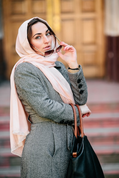 Mooie jonge vrouw in een jas met een tas poseren Gratis Foto