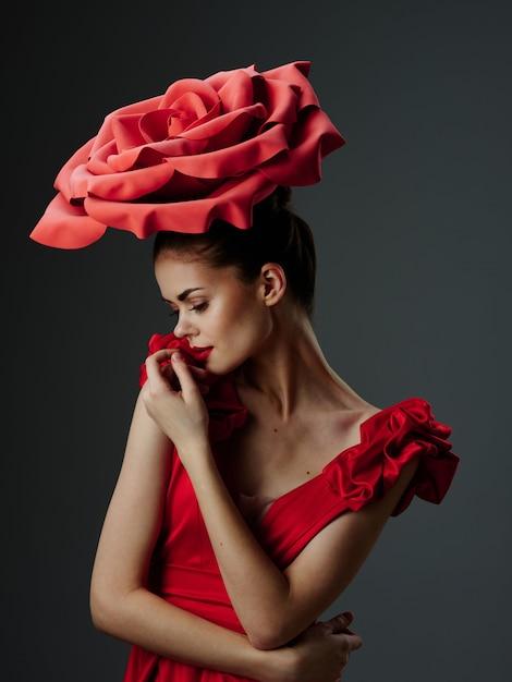 Mooie jonge vrouw in een luxe jurk met rozen, rozenblaadjes, stijlvolle afbeelding, rode lippenstift Premium Foto