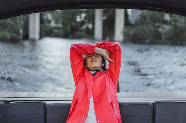 Mooie jonge vrouw in een rode regenjas rijdt een prive-jacht. stockholm, zweden Gratis Foto