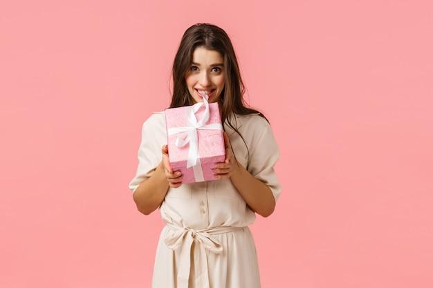 Mooie jonge vrouw in een stijlvolle lichte jurk, bijtend geschenkdoos en glimlachen, willen open, verleidelijk zien wat binnen verrassing aanwezig is, roze achtergrond Premium Foto