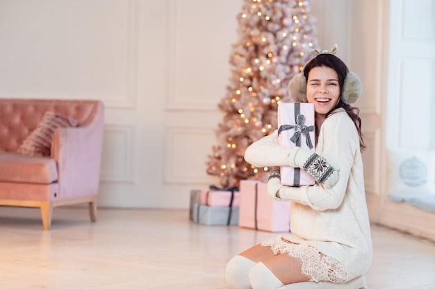 Mooie jonge vrouw in een witte jurk gooit een geschenk Gratis Foto