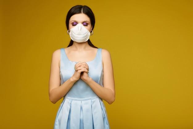 Mooie jonge vrouw, in gezichtsmasker en jurk, met gelede armen en gesloten ogen bidt brunette meisje in geneeskunde masker bidt voor genezing van griepepidemie Premium Foto
