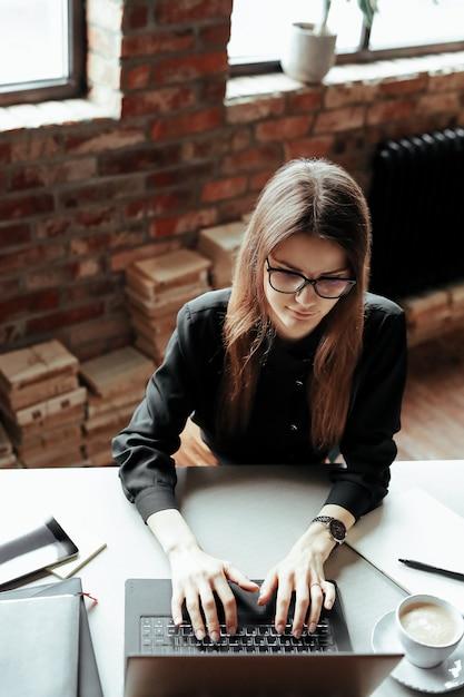 Mooie jonge vrouw in het kantoor aan huis. werken vanuit huis. telewerken concept Gratis Foto