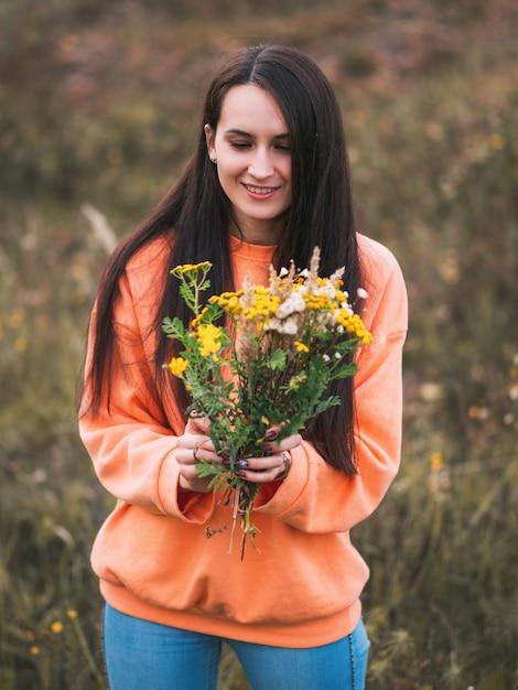 Mooie jonge vrouw in oranje hoodie in de herfstpark met een boeket van gedroogde bloemen Premium Foto