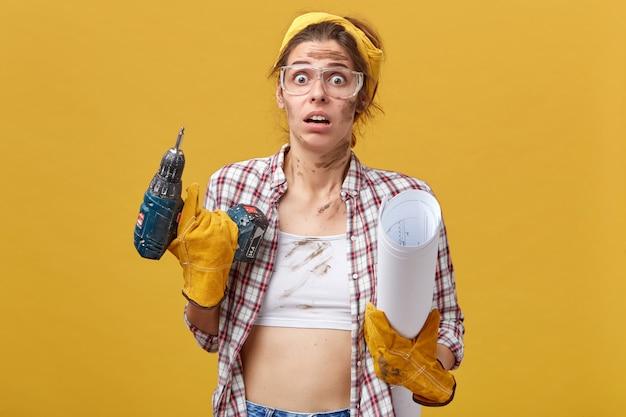 Mooie jonge vrouw in werkkleding met boor en blauwdruk met een angstige blik, zich realiserend dat ze het werk zelf zou moeten doen zonder de hulp van haar man die niet weet wat ze moet beginnen Gratis Foto
