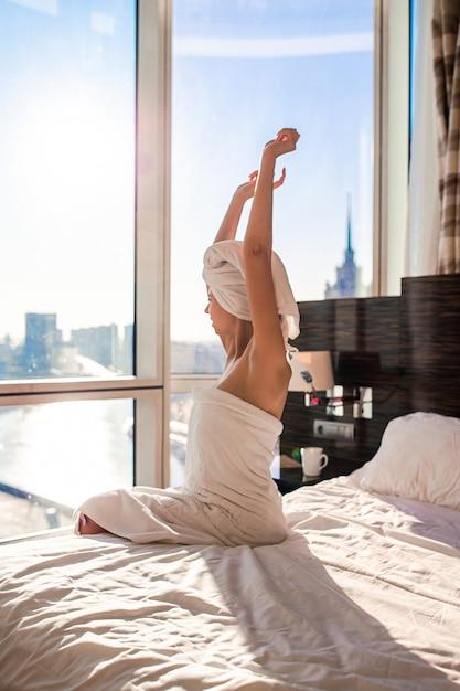 Mooie jonge vrouw in witte badhanddoek bij het hoofd ontspannen na douche op bed met kop van koffie Premium Foto