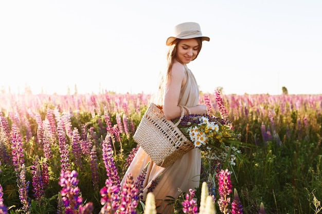 Mooie jonge vrouw in witte jurk en strooien hoed wandelen in bloem veld Gratis Foto