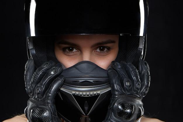 Mooie jonge vrouw in zwart leerhandschoenen en beschermende motorhelm. aantrekkelijke zelfbepaalde vrouwelijke motocycle racer die handen en lichaamsbescherming draagt tegen vallen en ongevallen Gratis Foto