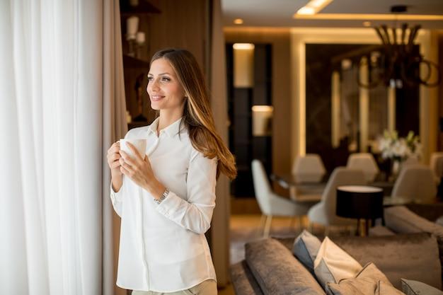 Mooie jonge vrouw koffie drinken en kijken door raam terwijl je in het appartement Premium Foto
