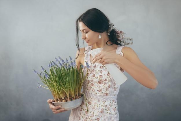 Mooie jonge vrouw lentebloemen in bloempot water geven Premium Foto