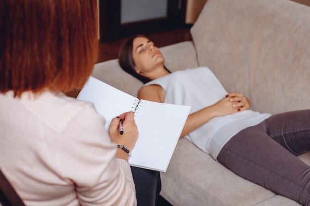 Mooie jonge vrouw liggend op de bank bij de receptie met een psychotherapeut. geestelijke psychische problemen. geestelijke problemen concept Premium Foto
