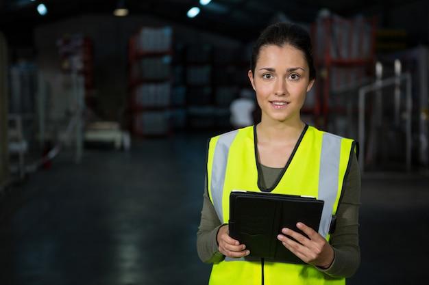 Mooie jonge vrouw met behulp van digitale tablet in fabriek Gratis Foto