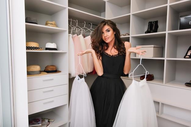 Mooie jonge vrouw met bruin lang krullend haar in een mooie garderobe rond kleding, hoeden, schoenen, witte pluizige rokken vast te houden, te beslissen wat te dragen. Gratis Foto