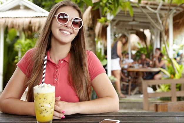 Mooie jonge vrouw met een charmante glimlach met een gelukkige en vrolijke uitdrukking, genietend van vakantie in een exotisch land Gratis Foto