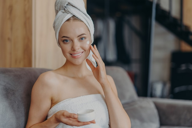 Mooie jonge vrouw met een gezonde gladde huid past gezichtscrème toe, draagt een gewikkelde handdoek op het hoofd na het nemen van een douche, vormt op comfortabele bank. Premium Foto