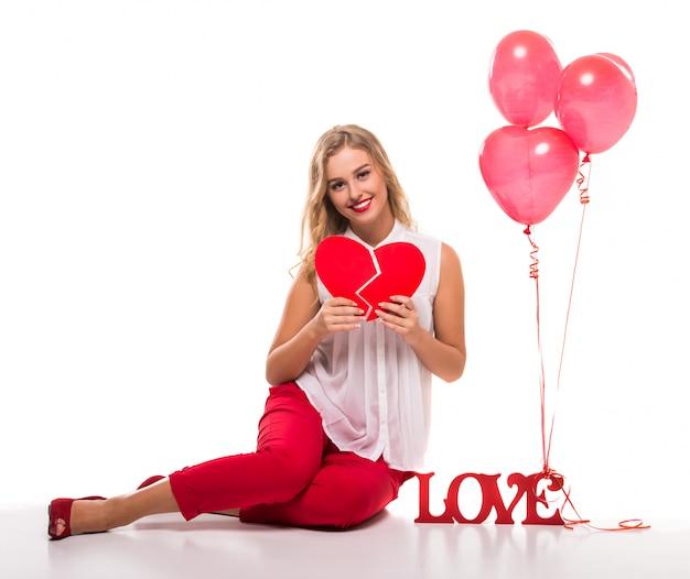 Mooie jonge vrouw met een teken het woord liefde. Premium Foto