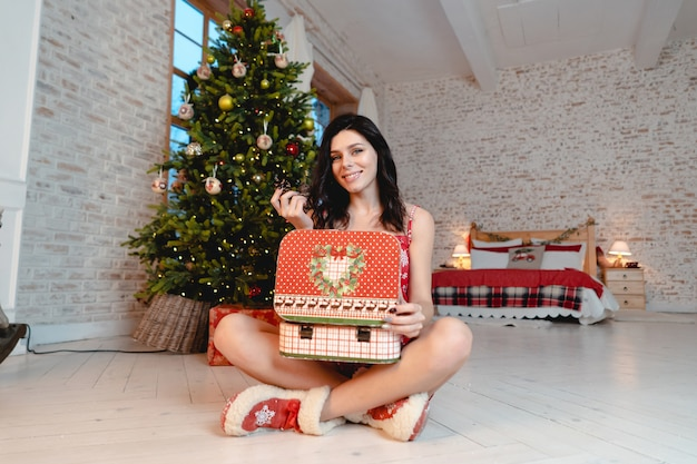 Mooie jonge vrouw met geschenken op de kerstboom Gratis Foto