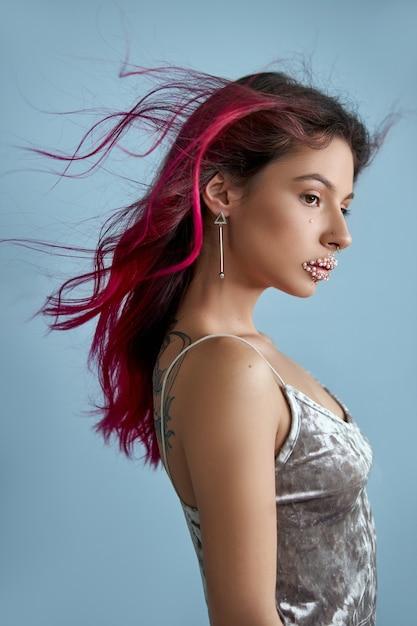 Mooie jonge vrouw met geverfd haar paars rode kleur, heldere schoonheid make-up close-up. sterk gekleurd haar Premium Foto