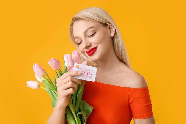 Mooie jonge vrouw met gift card en bloemen op kleur oppervlak Premium Foto