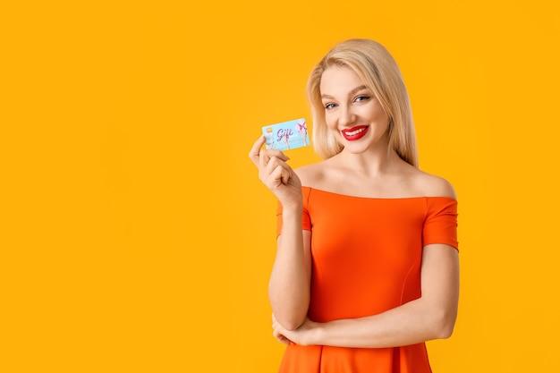 Mooie jonge vrouw met gift card op kleur oppervlak Premium Foto