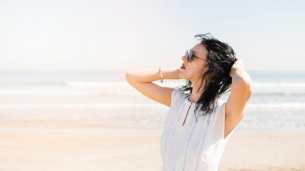 Mooie jonge vrouw met hand op haar hoofd staande in de buurt van de zee op het strand Gratis Foto