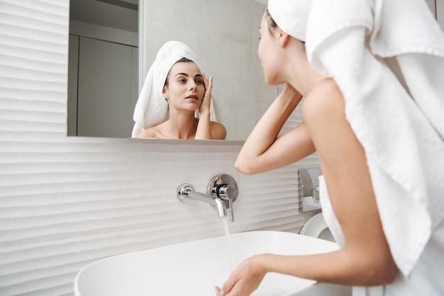 Mooie jonge vrouw met handdoek op haar hoofd die zich bij de badkamers bevinden, haar gezicht in een spiegel onderzoeken Premium Foto