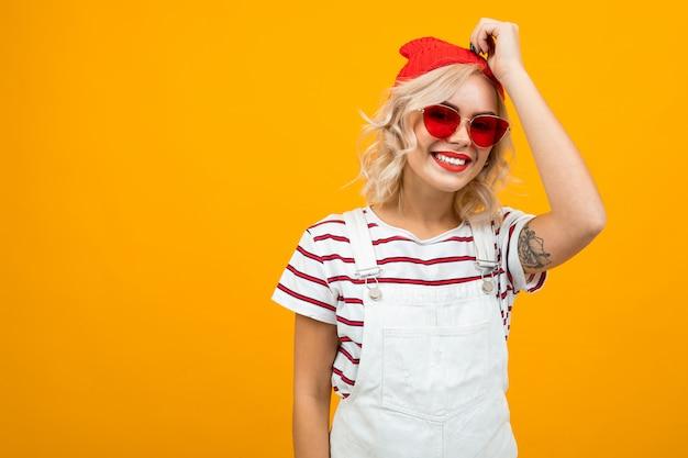 Mooie jonge vrouw met kort blond krullend haar en lichte make-up in witte overall. rode zonnebril en rode hoed gebaren en glimlacht, portret geïsoleerd op oranje Premium Foto
