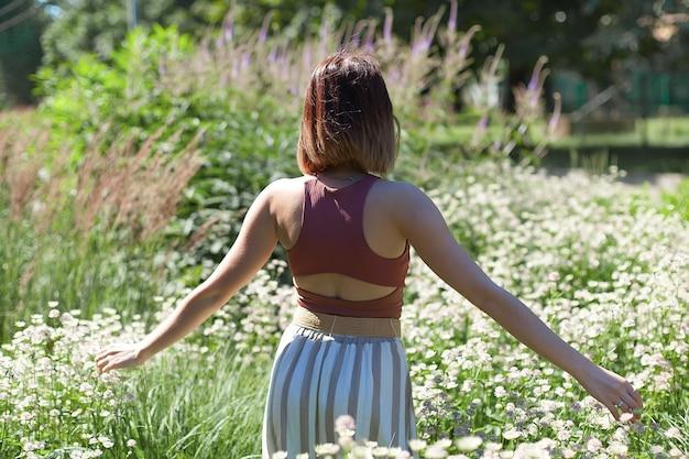 Mooie jonge vrouw met lang krullend haar gekleed in boho-stijl jurk poseren in een veld met paardebloemen. Premium Foto