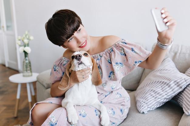 Mooie jonge vrouw met naakte make-up die met liefde haar beaglehond aanraakt en een foto van zichzelf maakt Gratis Foto