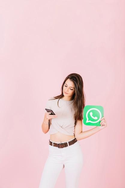 Mooie jonge vrouw met whatsapp pictogram met behulp van de mobiele telefoon Gratis Foto