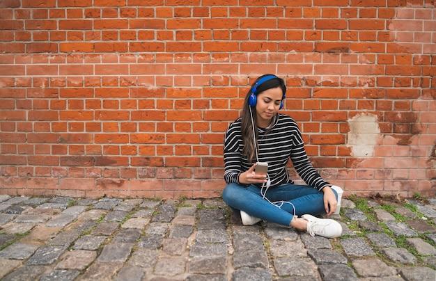 Mooie jonge vrouw muziek luisteren en met behulp van haar smartphone. technologie concept. stedelijke scène. Gratis Foto