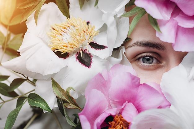 Mooie jonge vrouw omringd door pioenrozen bloemen zomer. mooi donkerbruin jong meisje dat van bloemen geniet. cover idee stemming Premium Foto