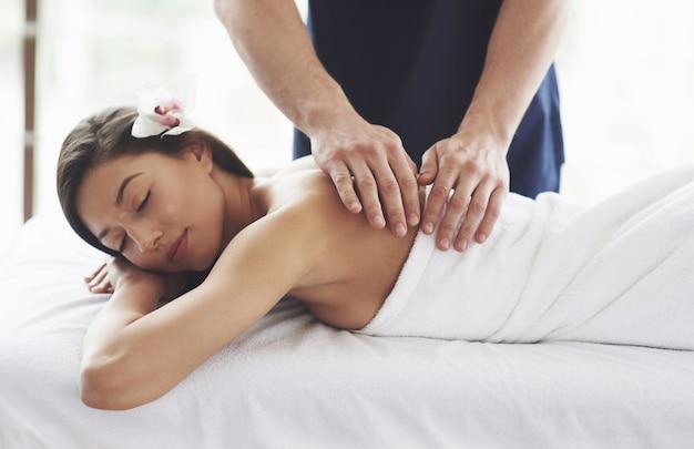 Mooie jonge vrouw ontspannen met handmassage in beauty spa. Gratis Foto