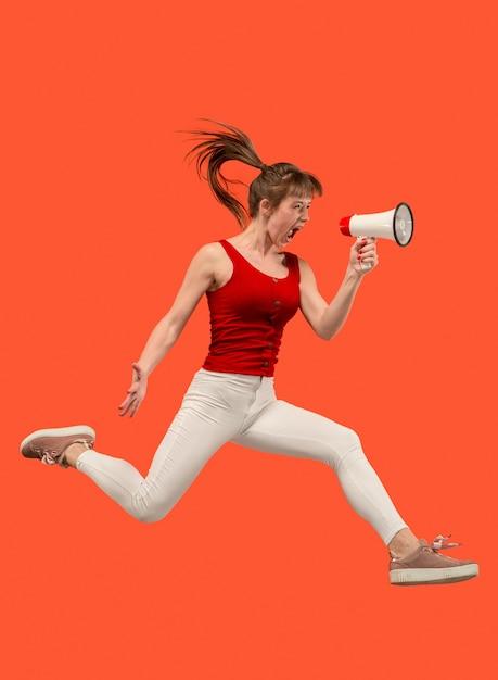 Mooie jonge vrouw springen met megafoon geïsoleerd dan rood Gratis Foto