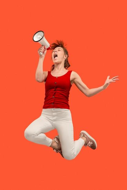 Mooie jonge vrouw springen met megafoon geïsoleerd dan rood. Gratis Foto