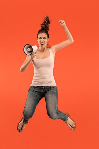 Mooie jonge vrouw springen met megafoon geïsoleerd op rode achtergrond. runnin meisje in beweging of beweging. menselijke emoties en gezichtsuitdrukkingen concept Gratis Foto
