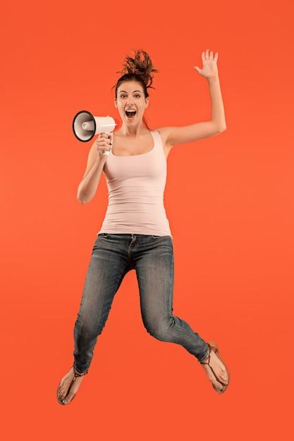 Mooie jonge vrouw springen met megafoon geïsoleerd op rode achtergrond. runnin meisje in beweging of beweging Gratis Foto