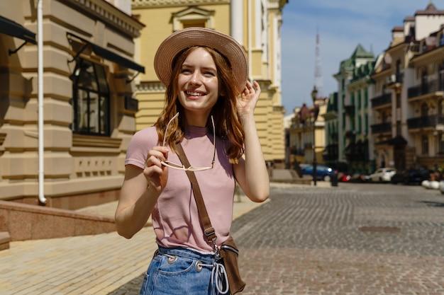 Mooie jonge vrouw toeristische aangename wandeling in het stadscentrum. Premium Foto